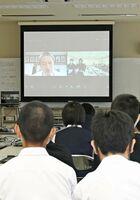 みどり台中の平塚真一郎校長(スクリーン左)の被災体験を画面越しに聞く川副中の生徒たち=佐賀市の同校