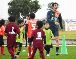 キャンプ地の子どもたちと笑顔で交流する金崎夢生選手=沖縄県の読谷村陸上競技場