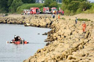 水難事故が発生したとみられる天建寺橋南の筑後川で、捜索活動を行う消防や警察=23日午後5時50分ごろ、三養基郡みやき町
