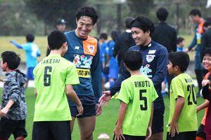 自身と同じ「たけし」という名前の子どもを見つけ、握手を求める金森健志選手(右)=沖縄県の読谷村陸上競技場
