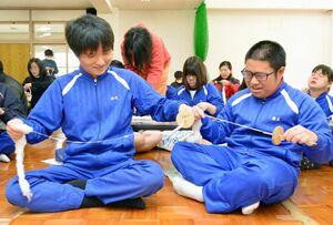 悪戦苦闘しながら綿を紡ぐ生徒たち=佐賀市の大和特別支援学校