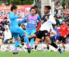 自陣で相手選手と激しく競り合うMF高橋(左)。中央はDF吉田=沖縄県の東風平運動公園サッカー場