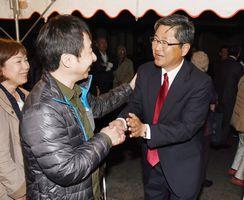 初当選の知らせを受け、支持者と握手をして笑顔を見せる古賀和浩さん(右)=7日午後10時15分ごろ、三養基郡基山町の事務所