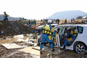 九州管区広域緊急援助隊合同訓練で、土砂崩れに巻き込まれた車から、乗っている人を救出する警察官=武雄市北方町