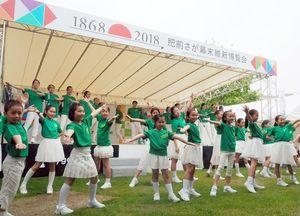 「鳥栖市の日」の会場で、元気いっぱい歌や踊りを披露するキッズミュージカルTOSUのメンバー=佐賀市の県立図書館南広場