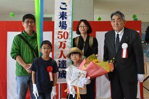 次世代エネルギーパークあすぴあの50万人目の来場者となった大和田七実さん(手に花束)の家族と玄海町の岸本英雄町長(右)=玄海町のあすぴあ