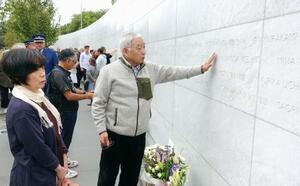ニュージーランド地震の追悼式典で堀田めぐみさんの名前が刻まれた石碑に触れる父和夫さんと母聖子さん(手前)=22日、クライストチャーチ(共同)