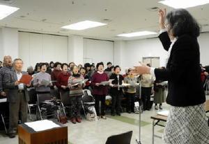 指揮者に合わせて合唱組曲「唐津」を歌う団員たち=唐津市西城内の唐津市民会館