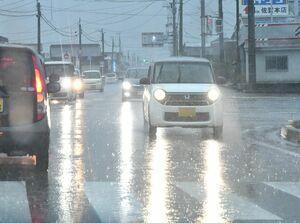 土砂降りの雨の中、ライトをつけて走行する乗用車の列=25日午前8時20分ごろ、佐賀市久保田町
