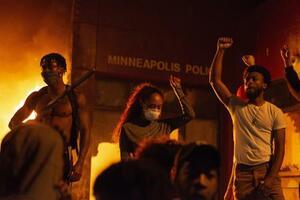 28日、米ミネソタ州ミネアポリスで、炎上する警察署前で拳を突き上げるデモ隊(ゲッティ=共同)