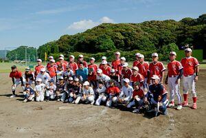 試合後、ホームベースを囲んで記念撮影をする両チームの選手たち=武雄市の白岩球場