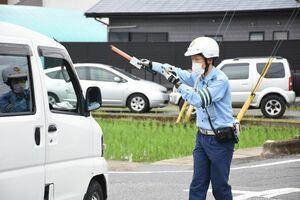 時間帯通行禁止の違反車両を止める警察官=佐賀市鍋島町の開成保育園付近