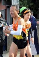 長女・来奈からたすきを受ける諸田雄一郎(手前)。長男・雄生も21区を走り、親子3人でたすきリレー=22―23区中継所