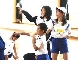 バドミントンのシャトルを使ったゲームを楽しむ神埼清明高生徒と西郷小児童=神埼市の西郷小