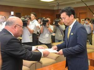 石倉秀郷県議会議長から、オスプレイ配備計画の受け入れを求める決議文を受け取る山口祥義知事(右)=3日午後、県議会議長室