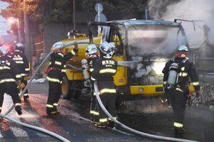 出火した散水車に放水する消防隊員=5日午前5時10分ごろ、唐津市北城内