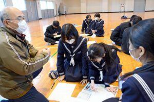 多久島文樹デスクから具体的なアドバイスを受ける生徒たち=有田町岩谷川内の有田中