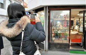街を歩きながら観光スポットなどを撮り、地域情報サイトに投稿する参加者=佐賀市呉服元町