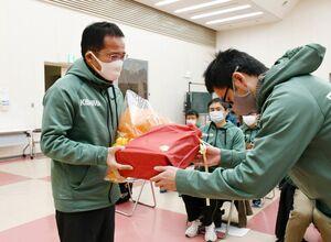 選手から花束や記念品を受け取り、感極まる杵島郡チームの小野勉監督(左)=江北町公民館