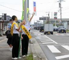 「追突注意」の看板を高く掲げて通勤ドライバーにアピールする有明中の生徒ら=白石町の国道207号「有明中学校前交差点」