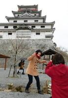 唐津城の前でアニメのシーンを再現し、記念撮影する女性ファン=唐津市東城内