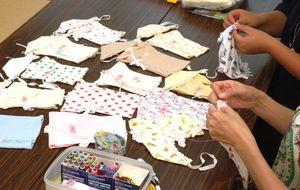 死産の子に着せるベビー服を作る「にこにこ257の会」のメンバー。送料や材料費に充てる支援金を募っている=佐賀市内の公民館