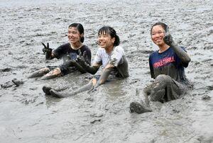 泥まみれになりながら、干潟体験を楽しむ高校生たち=鹿島市の七浦海浜スポーツ公園