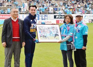 鳥栖MFクエンカに記念パネルを手渡す高本朋子さん(右から2人目)と夫の義史さん(右)。左は佐賀新聞社の坂田勝次常務