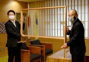 樺島雄大理事長(左)から飛沫防止ガードを受け取る秀島敏行市長=佐賀市役所来賓室