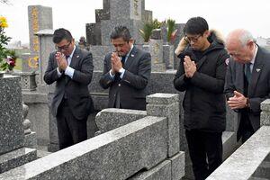 坂田道孝さんの墓前で手を合わせる竹原稔社長(左から2番目)や高橋義希選手(同3番目)らチーム関係者=佐賀市の善興寺
