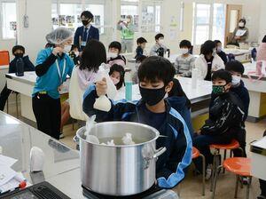 ポリ袋でご飯を炊く方法を学ぶ児童たち=鹿島市の明倫小