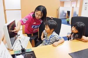 株の動きを観察する小学生ら=佐賀市のSMBC日興証券佐賀支店