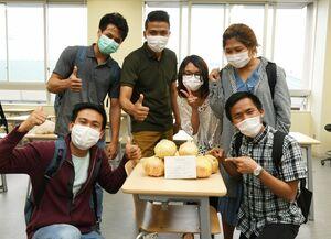 県職員有志から「お裾分け」のタマネギをもらい、喜ぶ留学生ら=佐賀市の西九州大短期大学部