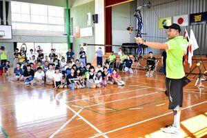 小学生との交流事業で、アーチェリーを披露するタイのパラ・アーチェリーの選手=昨年9月、佐賀市の西与賀小