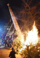 正月飾りに点火しながら、巨大たいまつを棒や縄で立てる消防団員=7日夜、唐津市十人町の唐津天満宮