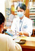 処方箋と一緒に詐欺被害防止のチラシを手渡し、注意を呼び掛ける薬剤師=小城市三日月町のタイヘイ薬局メディカルモールおぎ店
