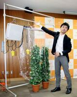 光合成の計測システムについて説明する愛媛大植物工場研究センターの高山弘太郎教授=9日、松山市