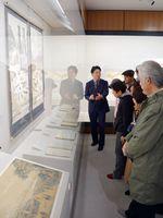 鍋島直正の業績について学芸員から説明を受ける来場者=佐賀市の佐賀城本丸歴史館