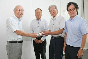 織口会長(右から2人目)から目録を受け取る吉野会長(左)=佐賀市の佐賀市国際交流協会