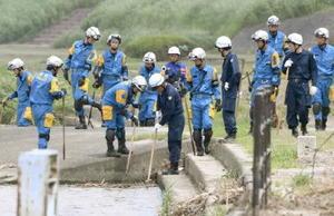 福岡県久留米市の筑後川沿いを捜索する警察官=20日