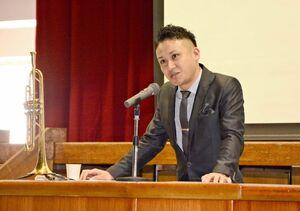 立志式に合わせて、夢や仲間の大切さを語ったトランペット奏者の平慶久さん=吉野ヶ里町の三田川中