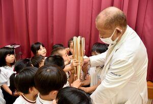 平松克輝理事長が持参したトーチを間近で見る園児たち=小城市のいわまつ保育園