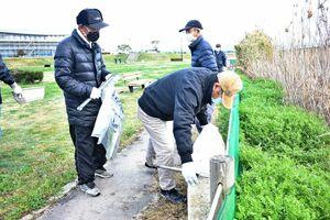 ごみ袋や火ばさみを持って、清掃活動に取り組む参加者=佐賀市川副町の三重津海軍所跡