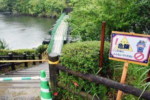 事故を受け、多久市が設置した進入禁止の立て看板。池をまたぐ桟橋(中央)の手すりには、落下を防ぐ網が施された=多久市北多久町の中央公園