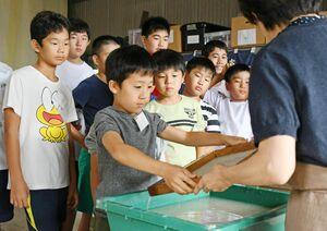 真剣な表情で紙すきを体験する児童=佐賀市の和紙工房「名尾手すき和紙」