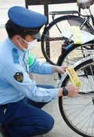 無施錠の自転車にワイヤ錠に見立てた紙を巻き、注意喚起する小城署員=小城市のJR小城駅