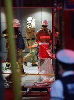 地下駐車場の消火設備の誤作動が起きたマンションで対応に当たる消防関係者ら=15日午後7時5分、東京都新宿区