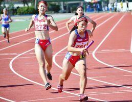 陸上女子1600メートルリレーで優勝した伊万里実チーム。第1走者の浦志光里(272)からバトンを受け取り走り出す濵部莉帆(右)=佐賀市のSAGAサンライズパークセカスタ