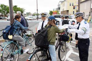自転車利用者に安全運転の啓発チラシを配る交通安全指導員=佐賀市の天神橋交差点
