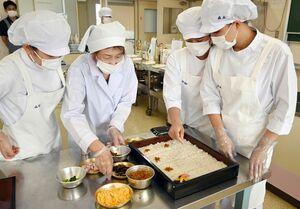 講師の副島たづ子さん(左から2人目)と須古ずしを作る学生たち=佐賀市の佐賀女子短大
